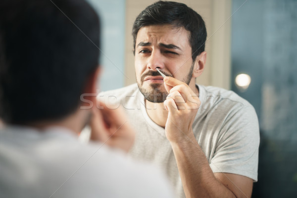 Handsome Man Trimming Nose Hair In Bathroom Stock photo © diego_cervo