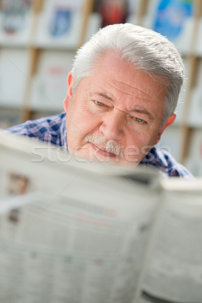Elderly man with mustache reading paper in library Stock photo © diego_cervo