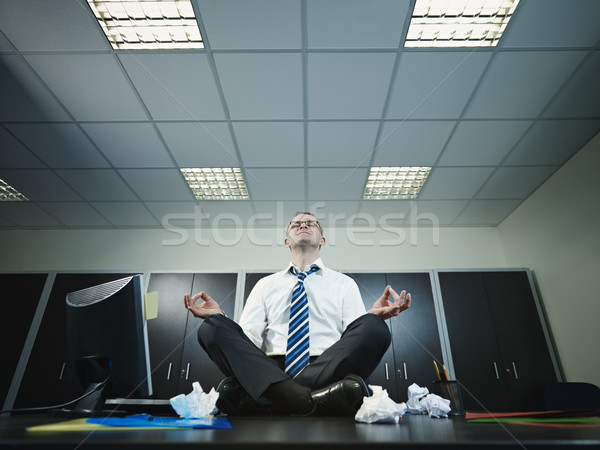 Stock photo: businessman doing yoga in office