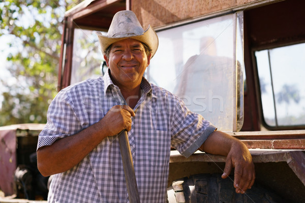 Portrait Happy Man Farmer Leaning On Tractor Looking At Camera Stock photo © diego_cervo