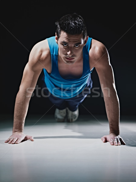 Man doing push-ups on black background Stock photo © diego_cervo