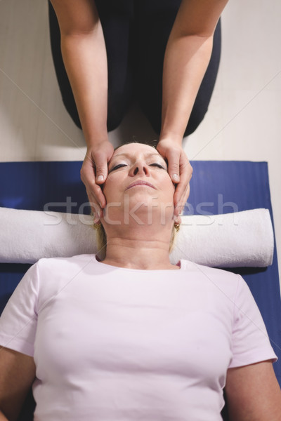 Young therapist doing reiki therapy to senior woman Stock photo © diego_cervo