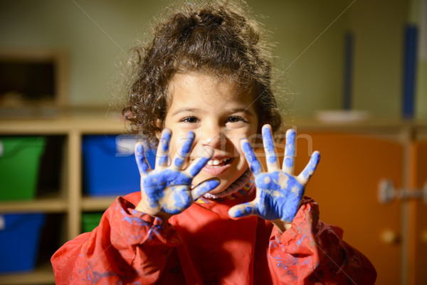 Stock photo: Happy little girl painting with hands in kindergarten