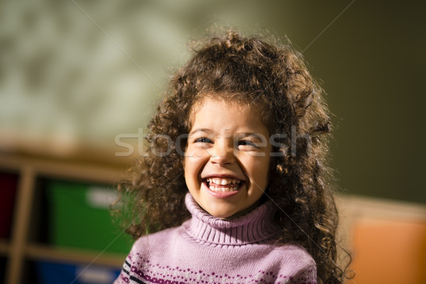 Stock photo: Happy female child smiling for joy in kindergarten