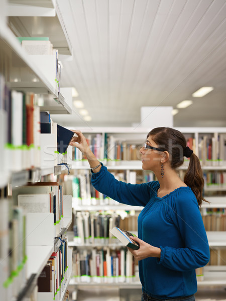 girl choosing book in library Stock photo © diego_cervo