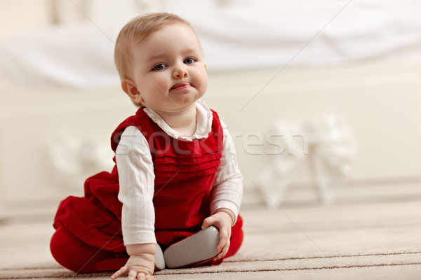 little girl sitting on carpet, looking at camera Stock photo © diego_cervo