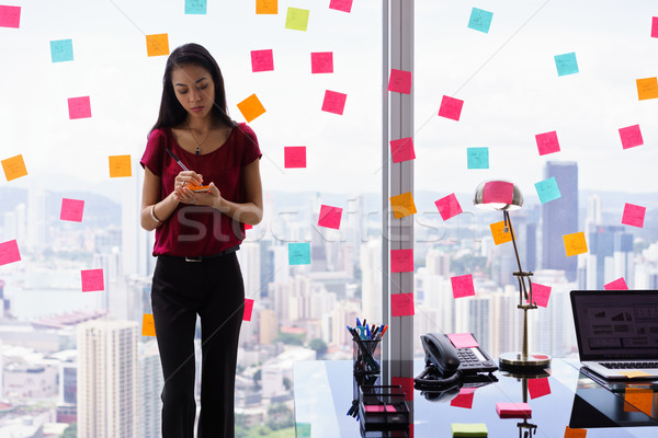 Chaotic Office With Secretary Writing Sticky Notes On Window Stock photo © diego_cervo