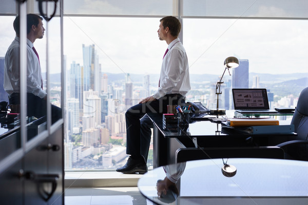 Business Person Sits On Desk Looking Out Of Office Window Stock photo © diego_cervo