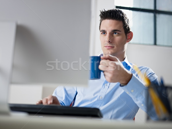 Stock photo: businessman drinking coffee in office