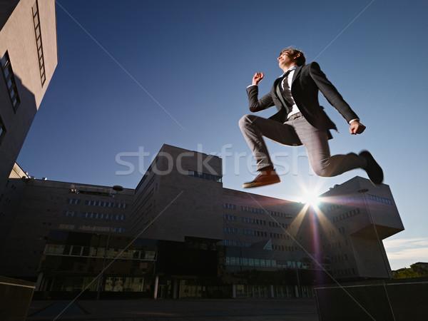 Biznesmen skoki uśmiechnięty na zewnątrz biuro młodych Zdjęcia stock © diego_cervo