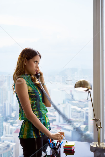 Young Latina Businesswoman With Wired Telephone In Modern Office Stock photo © diego_cervo