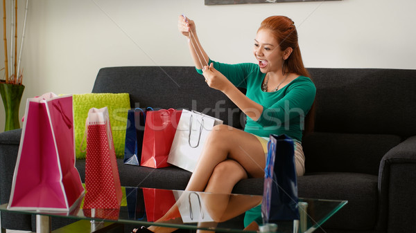 Latina Girl With Shopping Bags Tries Necklace On Sofa Stock photo © diego_cervo