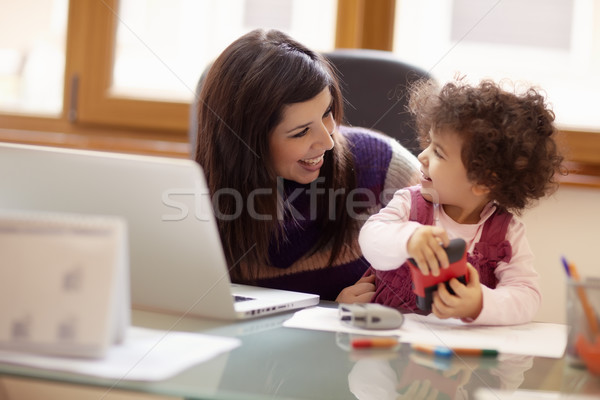 Stock photo: Multitasking mother with her daughter