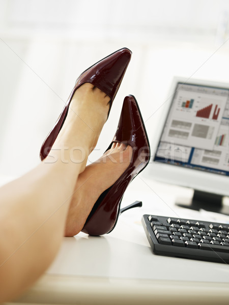 Stock photo: businesswoman with feet on table taking off shoes