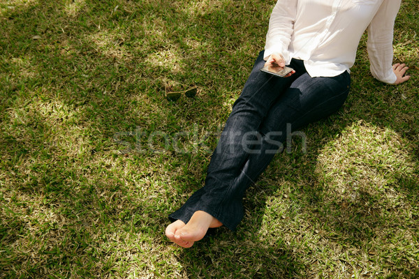 High Angle Woman Texting Mobile Phone Sitting Grass Park Stock photo © diego_cervo