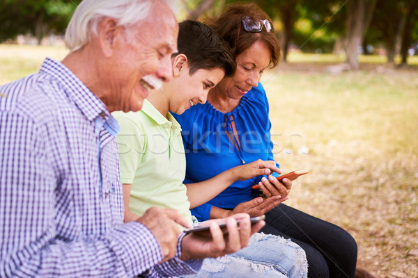 Child Helping Grandma Text Messaging On Mobile Phone Stock photo © diego_cervo