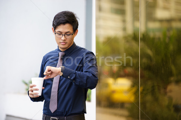 Portrait of chinese office worker checking time watch Stock photo © diego_cervo