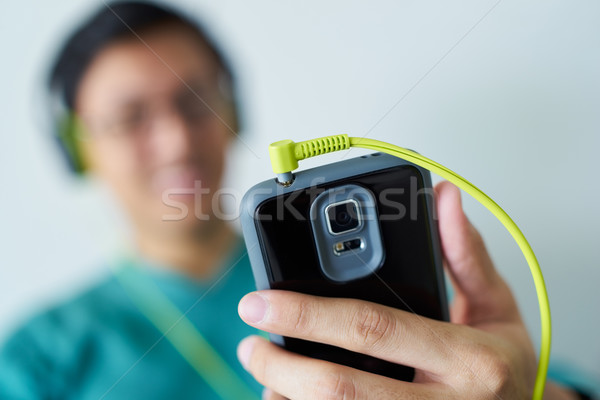 Chinese Man With Green Headphones Listens Music Podcast Phone Stock photo © diego_cervo