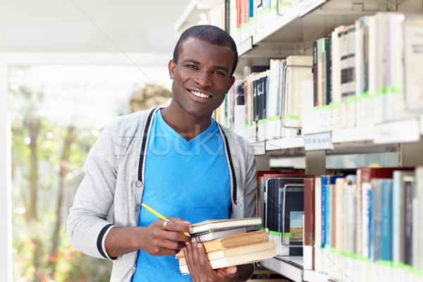 young african man smiling in library Stock photo © diego_cervo