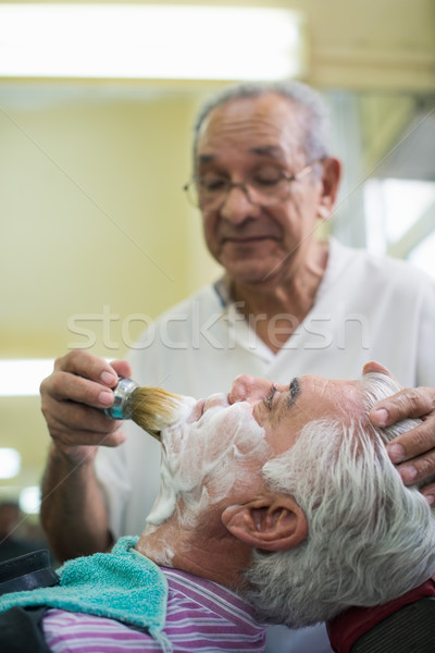 Senior man at work as barber shaving customer  Stock photo © diego_cervo