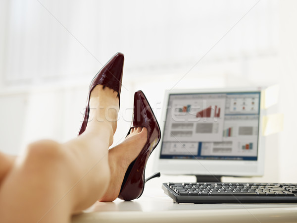Stock photo: business woman taking off shoes