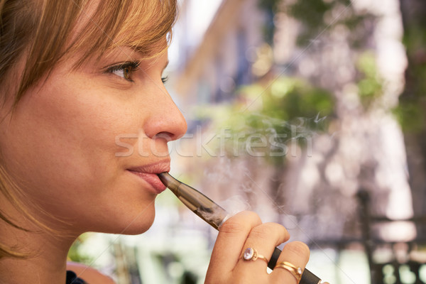 Young Woman Smokes E-Cig Electronic Cigarette Stock photo © diego_cervo