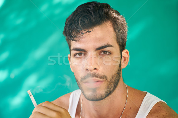 Young Hispanic Man Smoking Cigarette And Blowing Smoke Stock photo © diego_cervo