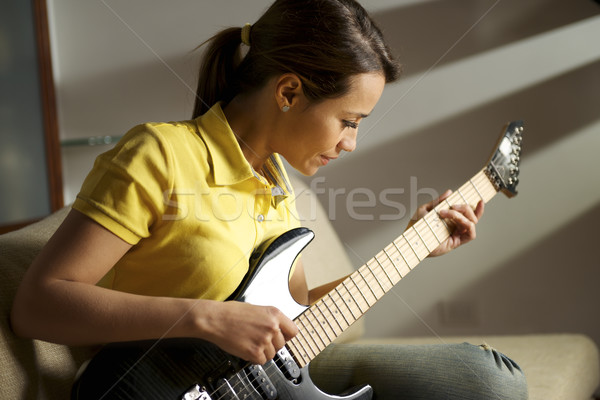 Stock photo: woman playing and training with electric guitar at home