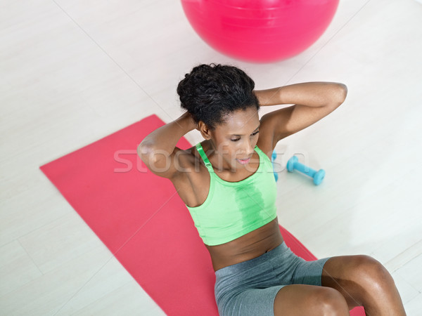 african woman doing series of crunch in gym Stock photo © diego_cervo