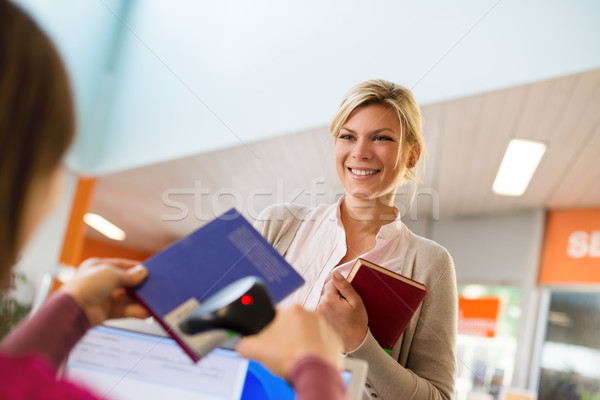 girl returning book to librarian in library Stock photo © diego_cervo