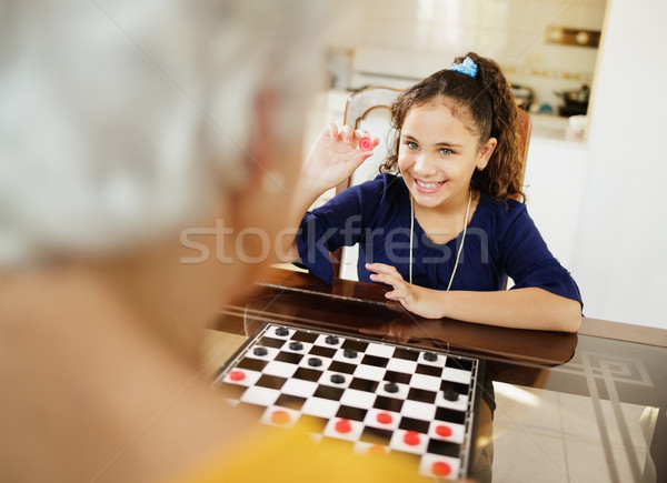Stock photo: Grandma Playing Checkers Board Game With Granddaughter At Home