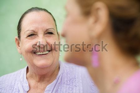 Two elderly women meeting and talking on park bench Stock photo © diego_cervo