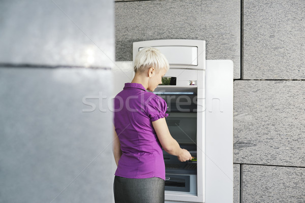 young woman withdrawing money with card at atm  Stock photo © diego_cervo
