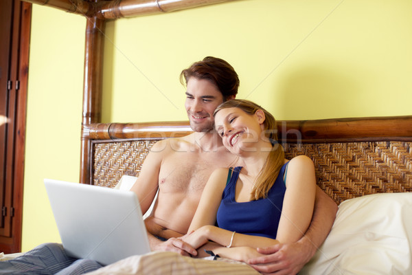 young couple lying on bed with pc Stock photo © diego_cervo
