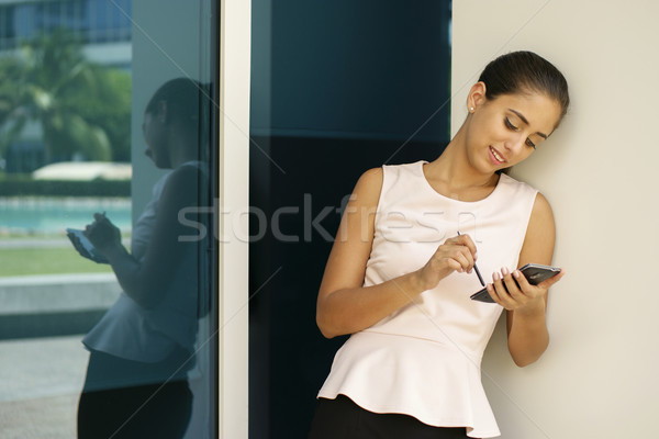Happy Business Woman Typing With Pen On Smartphone Stock photo © diego_cervo