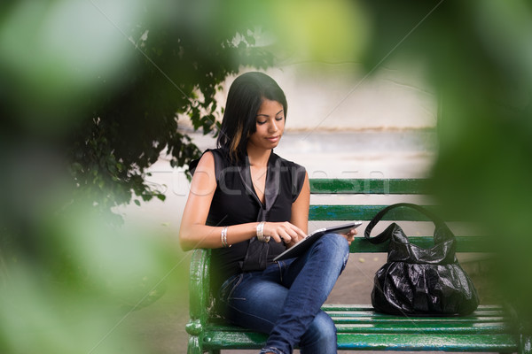hispanic woman with digital tablet pc on bench Stock photo © diego_cervo