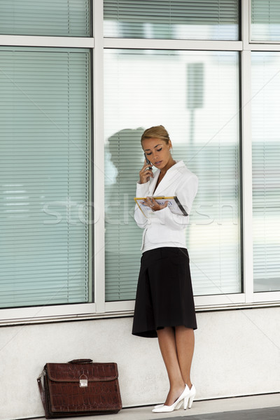 Stock photo: woman holding file speaking on telephone near office building
