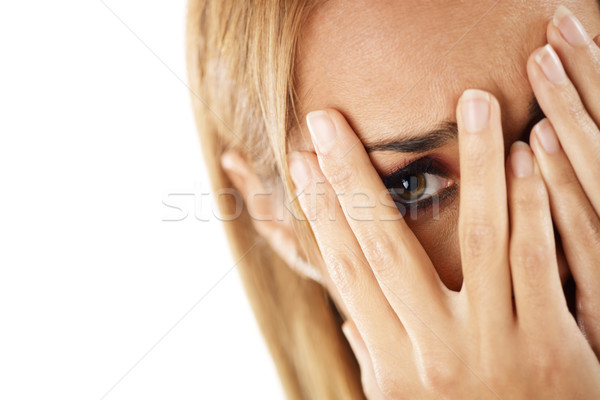 Stock photo: shy woman looking through fingers