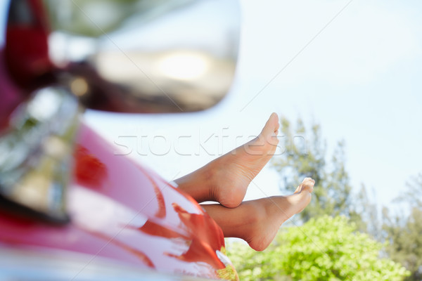 Stock photo: woman lying in cabriolet car with feet out of window