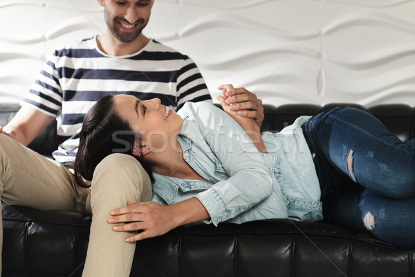 Happy Latino Couple Holding Hands And Smiling On Sofa Stock photo © diego_cervo