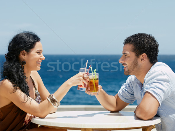 Stock photo: happy husband and wife toasting with cocktails