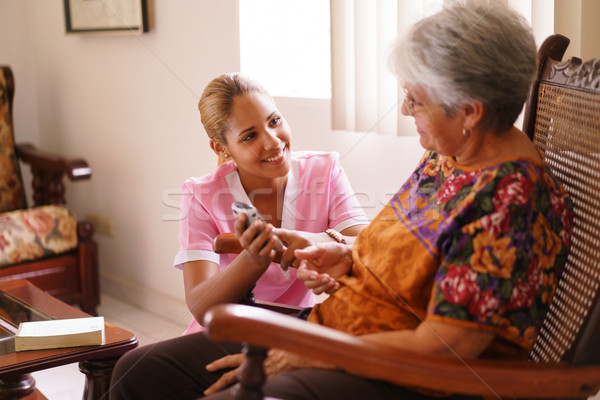 Hospice Nurse Helps Old Lady With Mobile Phone Call Stock photo © diego_cervo