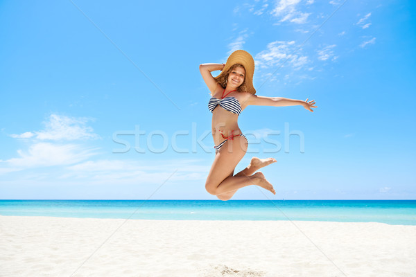 Woman with straw hat jumping mid-air at beach Stock photo © diego_cervo