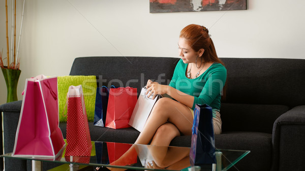 Latina Girl Peeps Into Shopping Bags On Sofa At Home Stock photo © diego_cervo