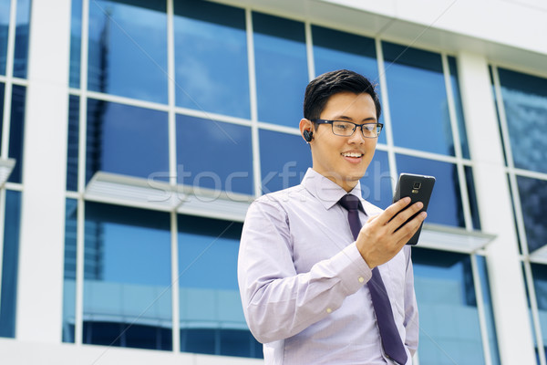 Businessman Talking Video Call On Mobile With Bluetooth Headset Stock photo © diego_cervo