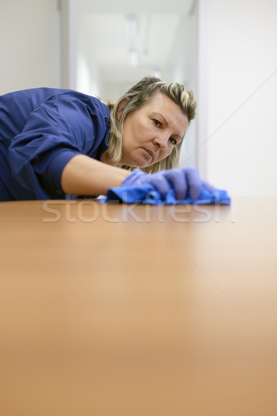 Professional female cleaner wiping table in office Stock photo © diego_cervo