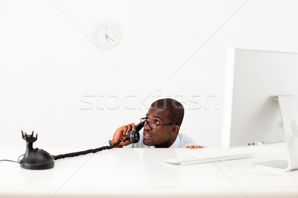 Stock photo: businessman hiding behind desk