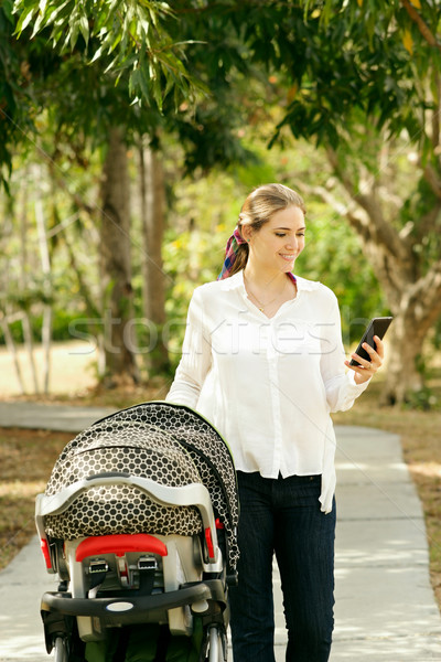 Mother With Baby In Pushchair Sending Message On Phone Stock photo © diego_cervo
