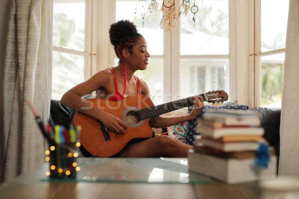Mixed Race Girl Singing And Playing Classic Guitar At Home Stock photo © diego_cervo