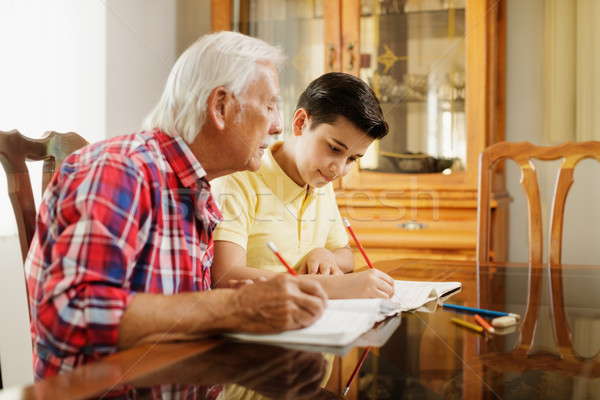 Little Boy Doing School Homework With Old Man At Home Stock photo © diego_cervo